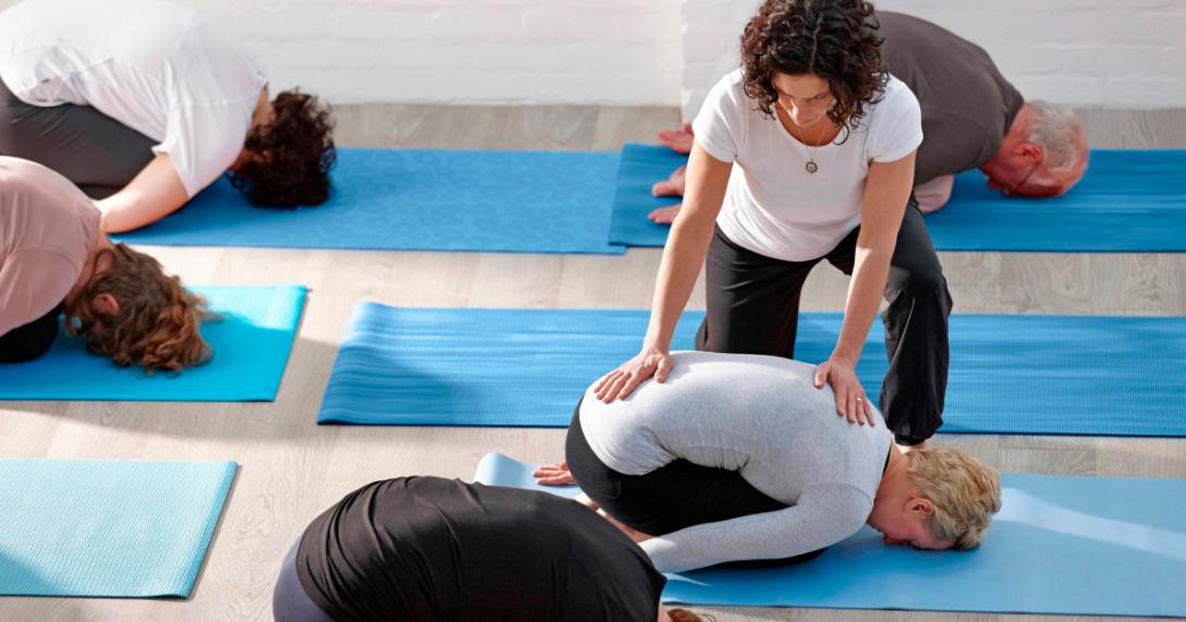 Yoga teacher adjusting in Childs pose Crop