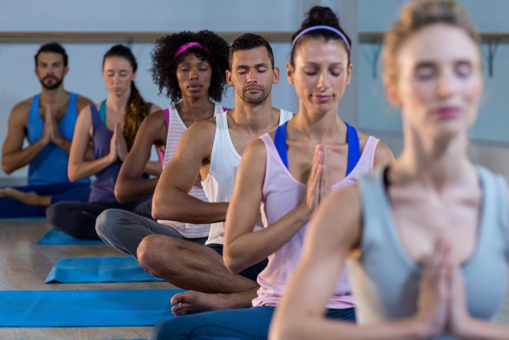 Group of people performing yoga in gym.jpeg