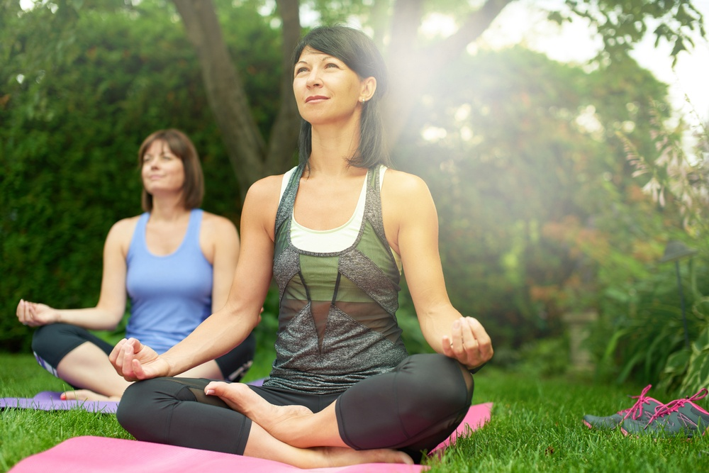 Two mature women keeping fit by doing yoga in the summer-1.jpeg